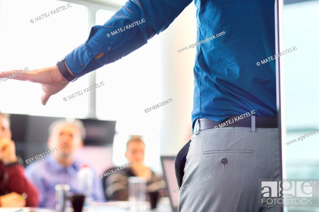 Stock Photo: Business man making a presentation at office. Business executive delivering a presentation to his colleagues during meeting or in-house business training.