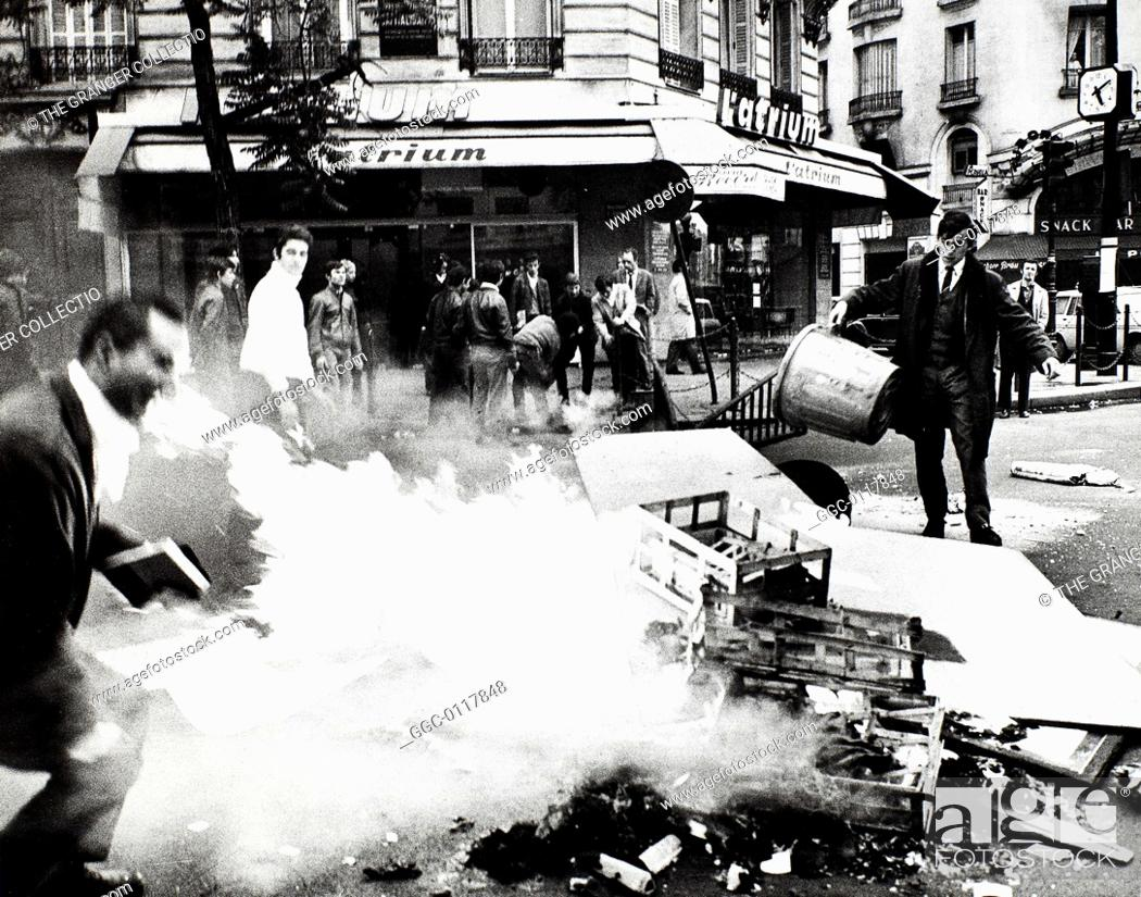 Stock Photo: PARIS STUDENT REVOLT, 1968.Students feeding the fire set to a barricade of garbage at Boulevard St. Germain on the Left Bank in Paris, France, 23 May 1968.
