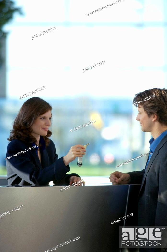 Stock Photo: Receptionist giving the key of a hotel room to a businessman.