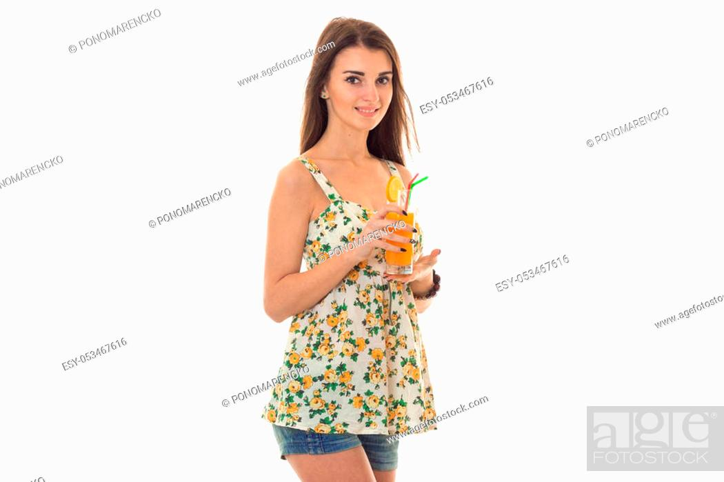 Stock Photo: beauty young girl in jeans shorts and sarafan with floral pattern drinks orange cocktail and looking at the camera isolated on white.