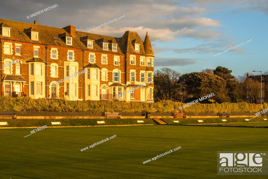 Stock Photo: Cliff Parade bowling green and terrace of houses at Hunstanton warn late evening sun, Norfolk, East Anglia, England, UK.
