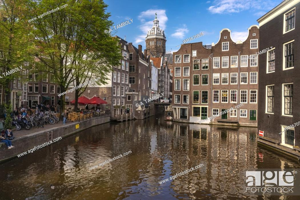 Stock Photo: Netherlands, North Holland, Amsterdam, Historic houses along canal in Binnenstad.