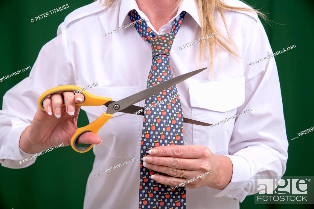 Stock Photo: Woman using scissors to cut a necktie in half for a joke.