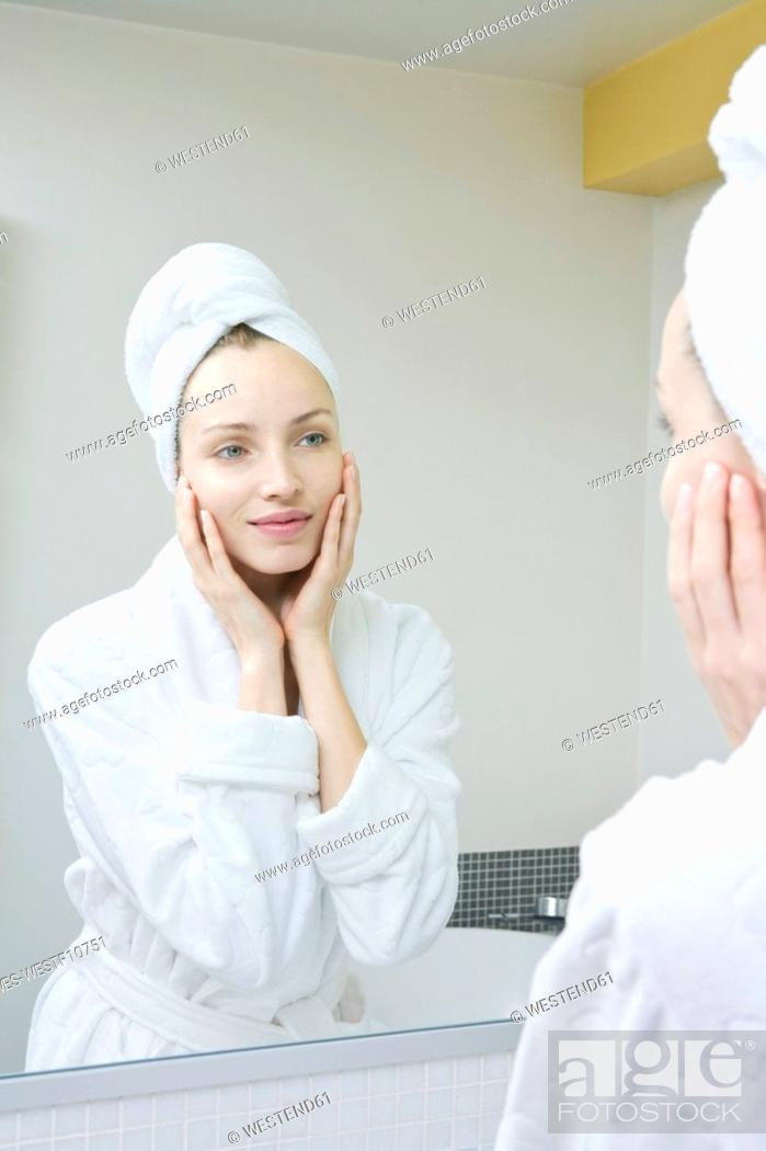 Stock Photo: Young woman looking in mirror, portrait.
