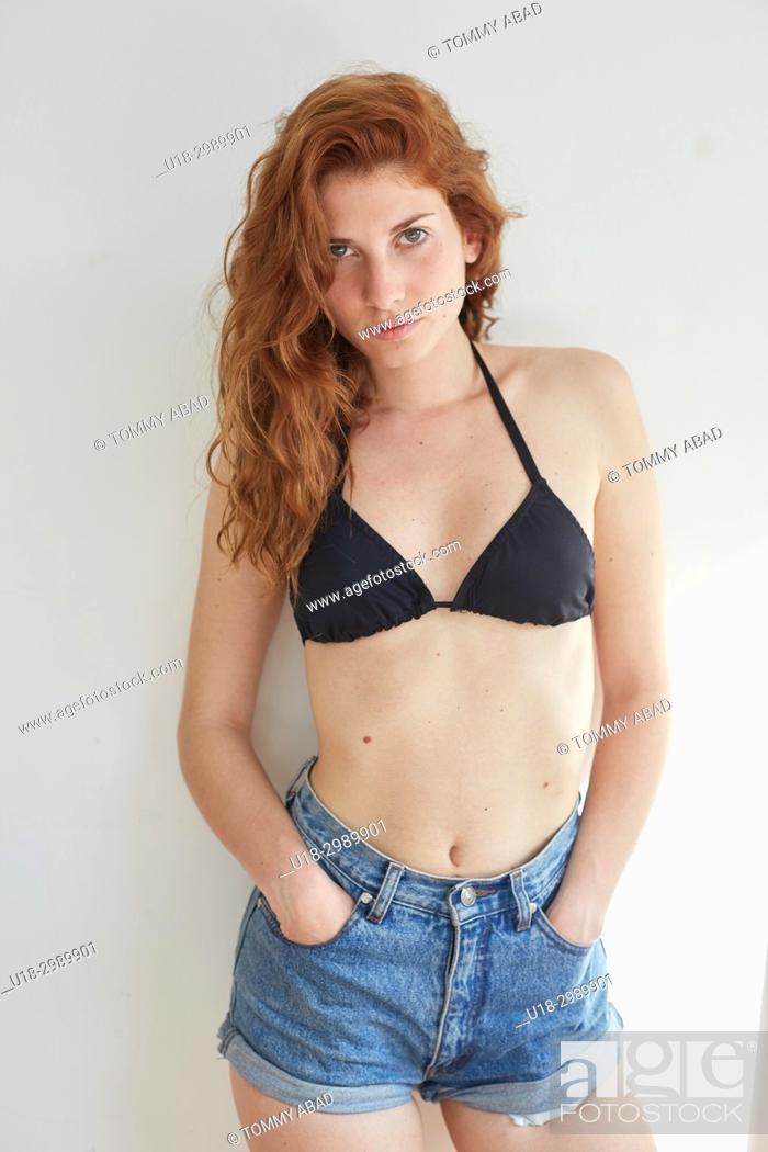Stock Photo: Three quarter length portrait of young redhead woman wearing black bikini and shorts, looking at camera.