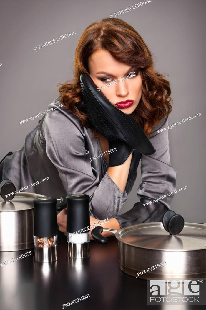 Stock Photo: Young woman looking disappointed, cooking.