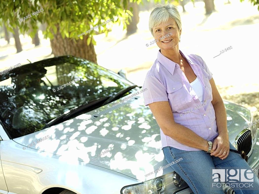 Stock Photo: Senior woman sitting on bonnet of convertible car, smiling, portrait tilt.