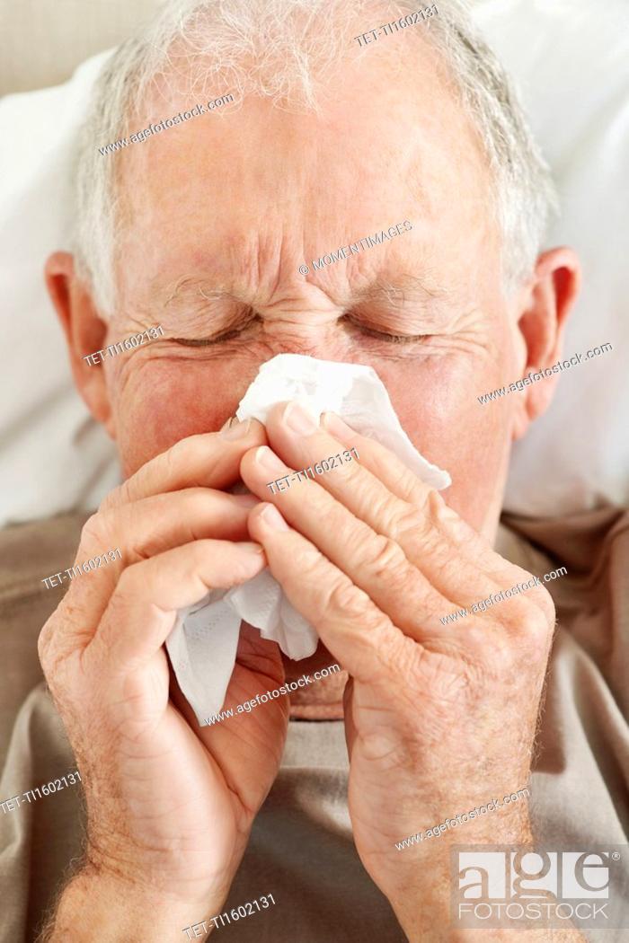 Stock Photo: Senior man blowing his nose.
