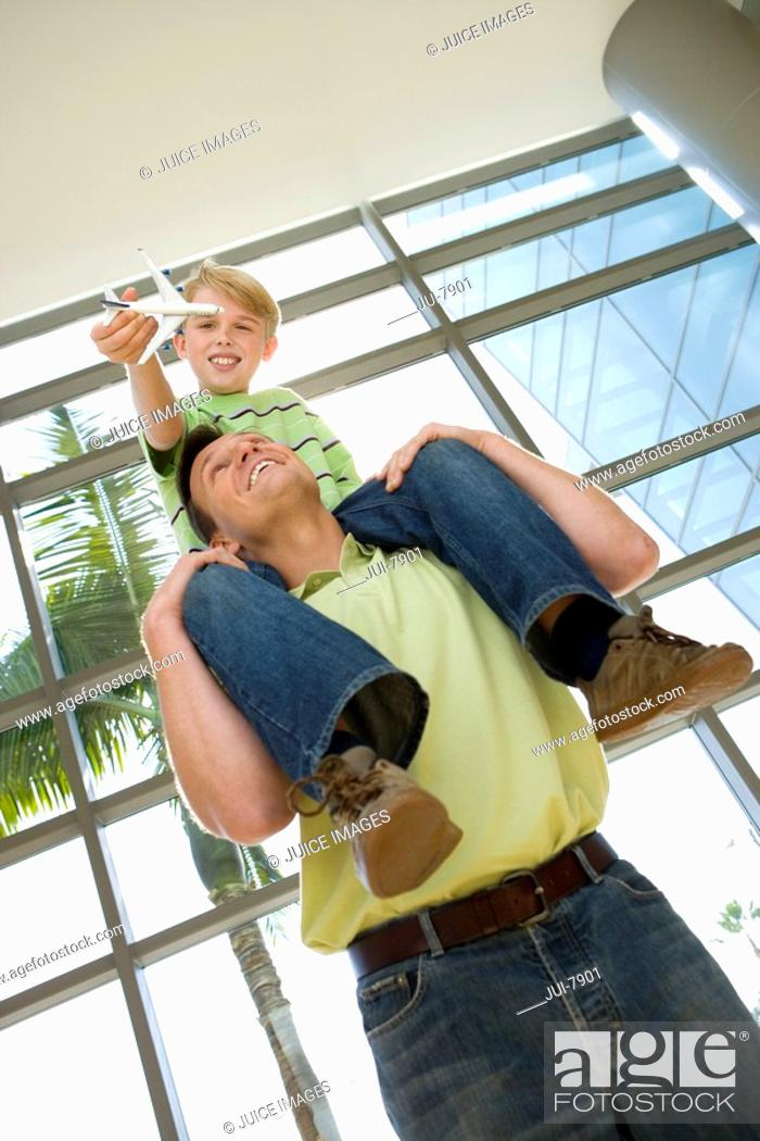 Stock Photo: Father carrying son 8-10 on shoulders in airport, boy holding toy aeroplane, smiling, low angle view tilt.