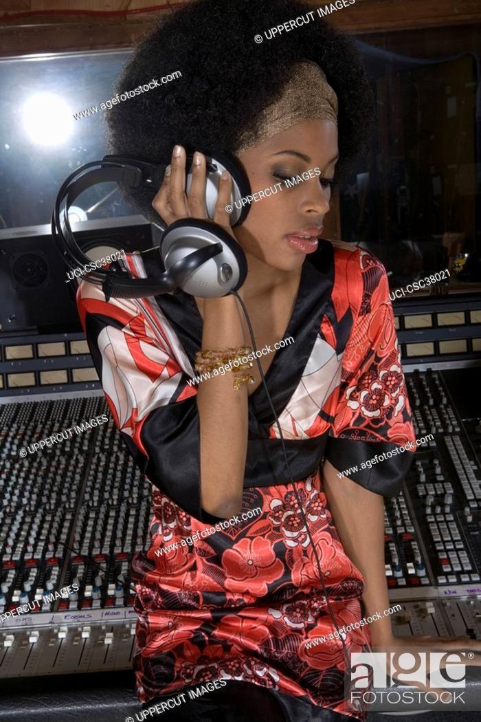 Stock Photo: Musician listening to headphones in recording studio.
