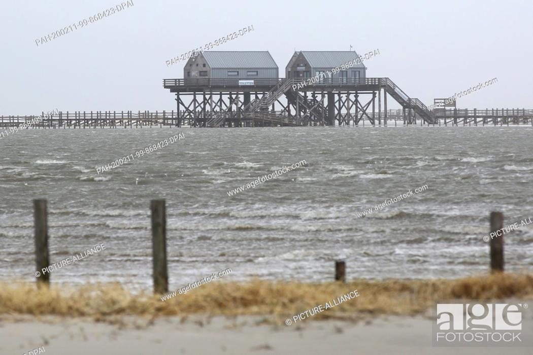 Stock Photo: 11 February 2020, Schleswig-Holstein, St. Peter-Ording: Rising water floods the beach of St. Peter-Ording. In the afternoon a storm surge is expected again on.