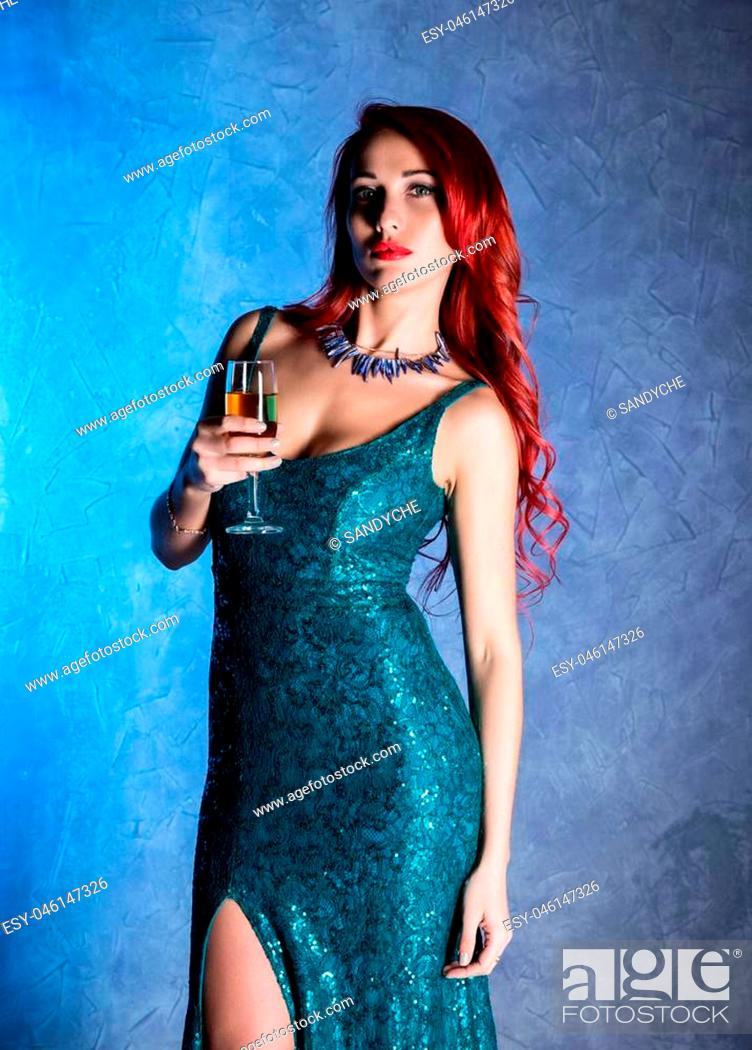 Stock Photo: Young sexy woman with big boobs in blue elegant dress holding wineglass with champagne.