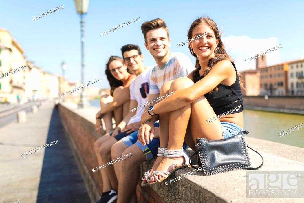 Stock Photo: Italy, Pisa, group of four happy friends sitting on a wall along Arno river.