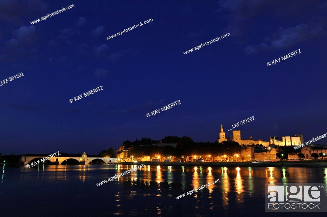Stock Photo: View over river Rhone to the bridge, city walls, cathedral Notre-Dame-des-Doms and papal palace at night, Avignon, Vaucluse, Provence, France, Europe.