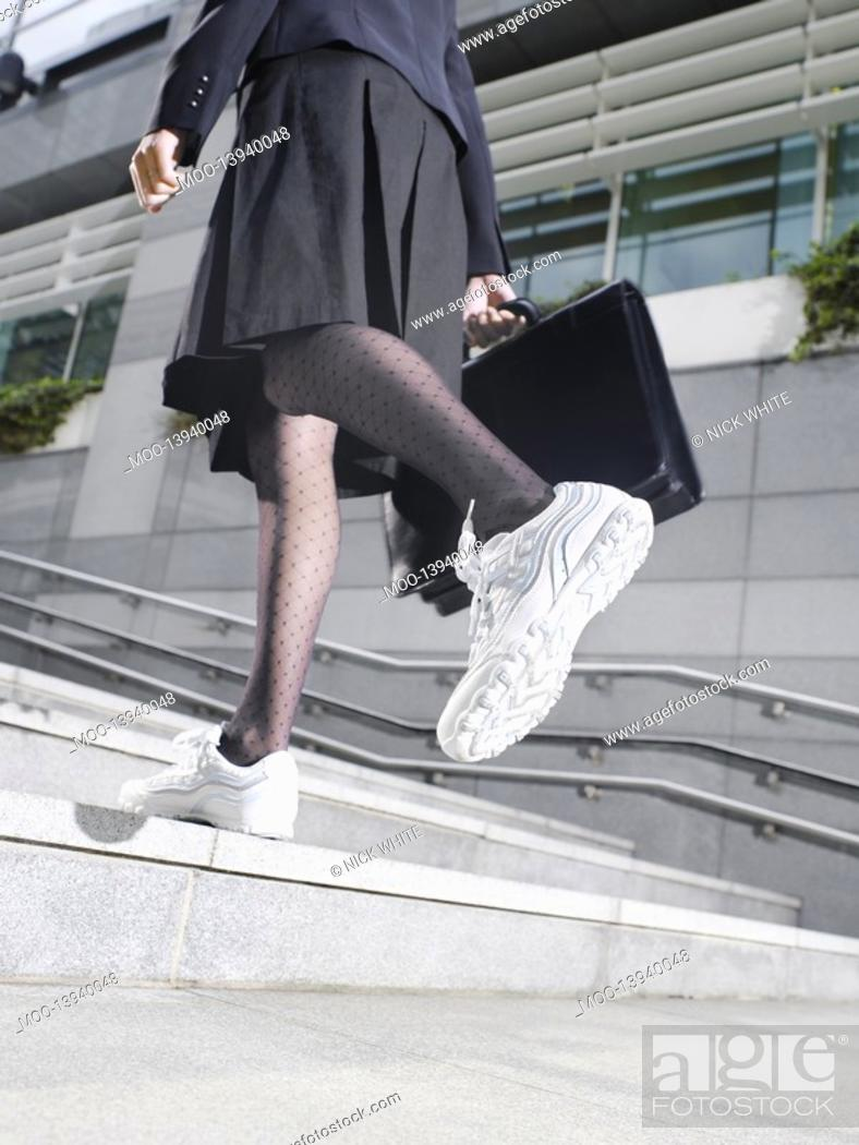 Stock Photo: Business woman wearing running shoes walking up steps low section low angle view.