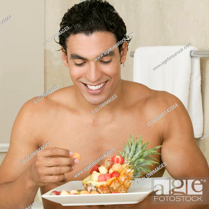 Stock Photo: Close-up of a young man eating fruits.