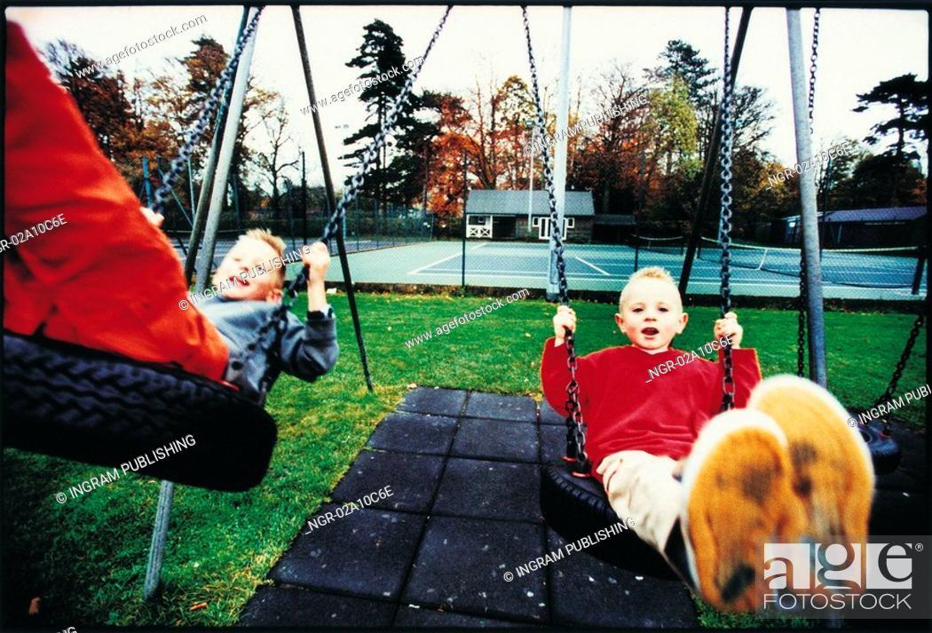Stock Photo: kids swinging at the playground.