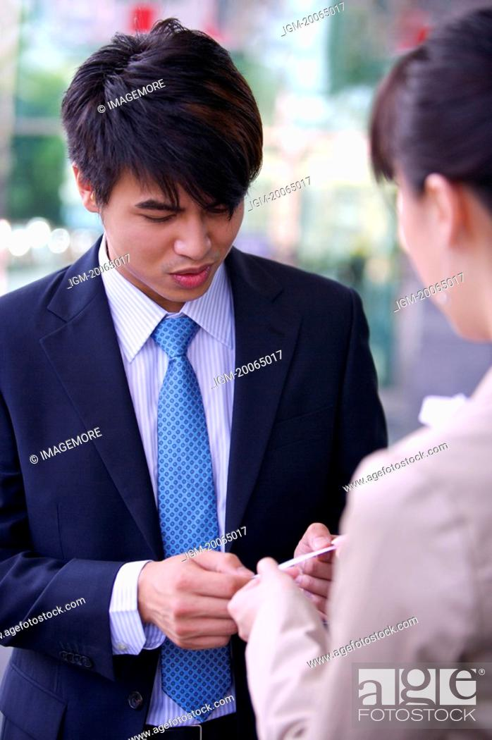 Stock Photo: Young woman and man delivering name card together.