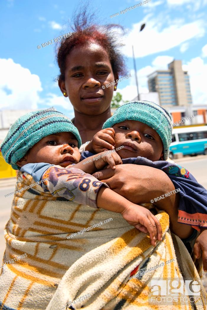 Stock Photo: A poor beggar carrying her baby twins in the streets of Antananarivo.