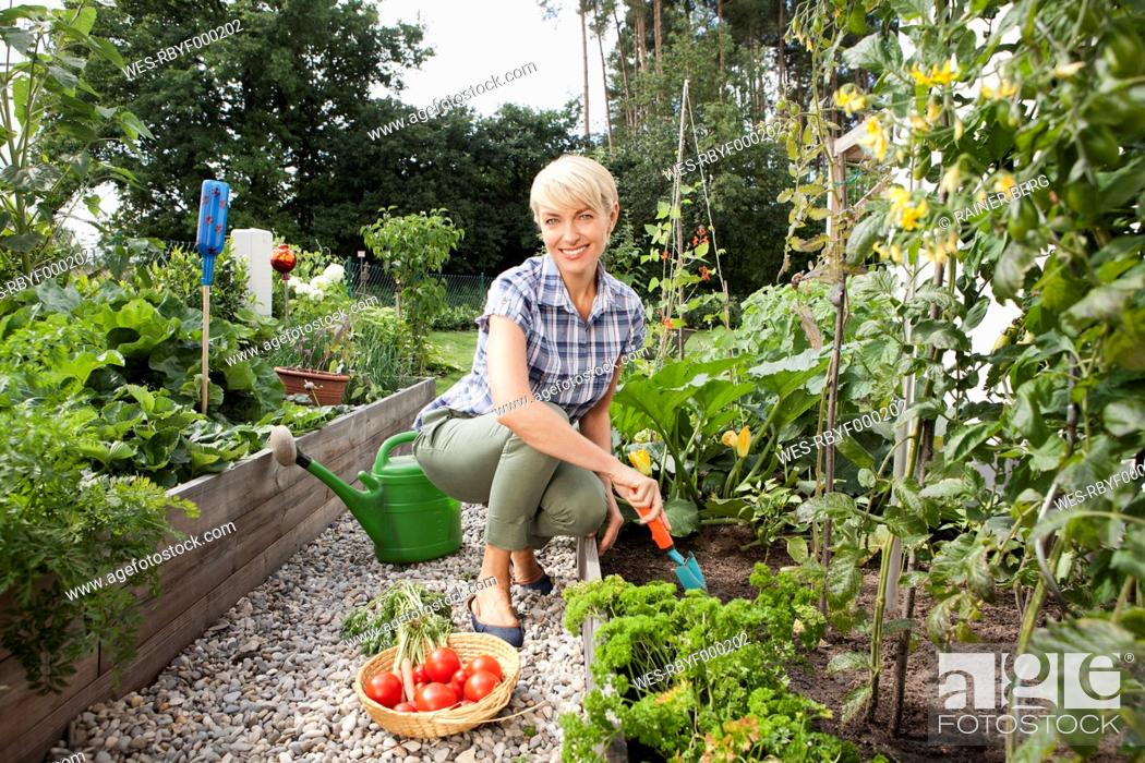 Stock Photo: Germany, Bavaria, Nuremberg, Mature woman with vegetables in garden.