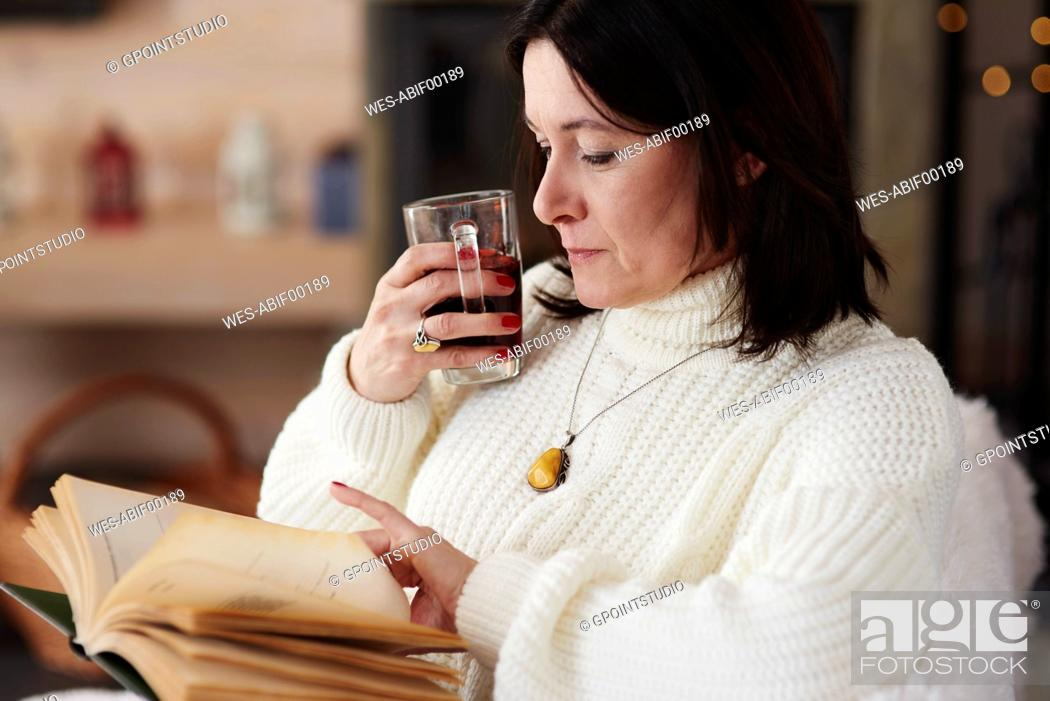 Stock Photo: Mature woman with a hot drink reading a book.