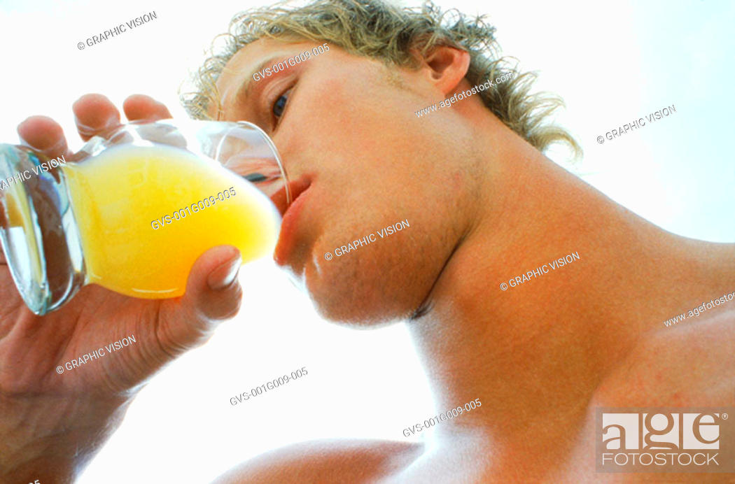 Stock Photo: Low angle view of a young man drinking juice from a glass.