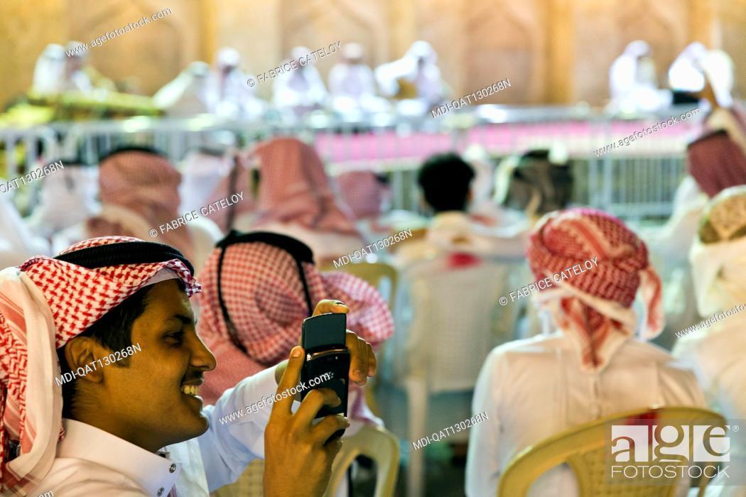Stock Photo: Qatar - Doha - Souq Waqif - Qatari recording an outdoor concert with mobile phones.