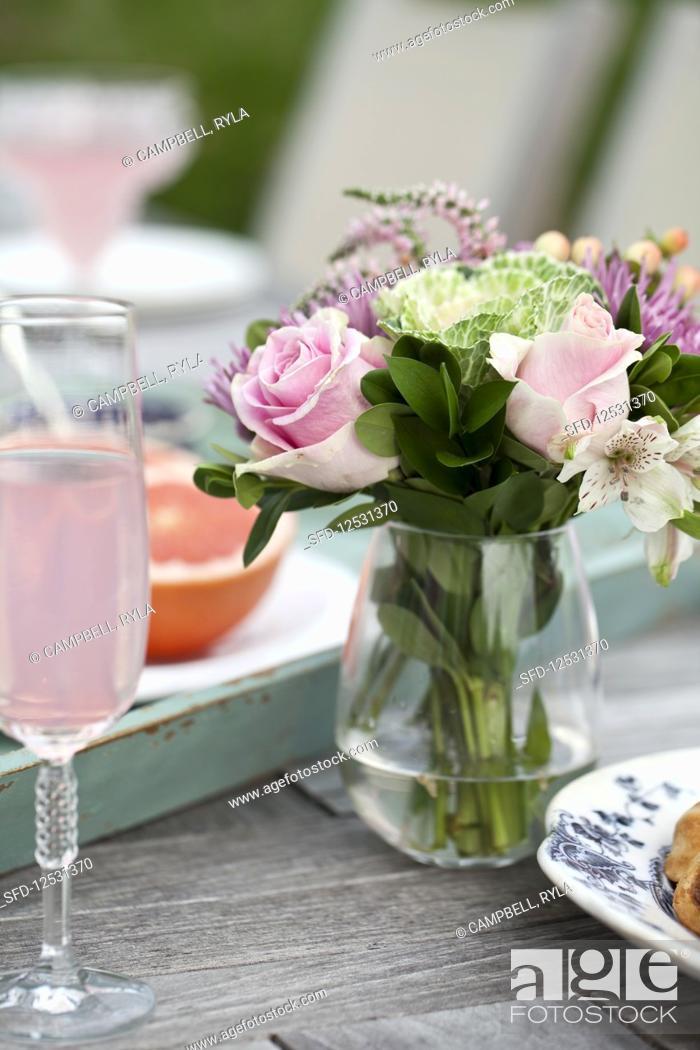 Stock Photo: Brunch outside, flowers, glasses of sparkling pink lemonade, grapefruit halves on an outdoor table.