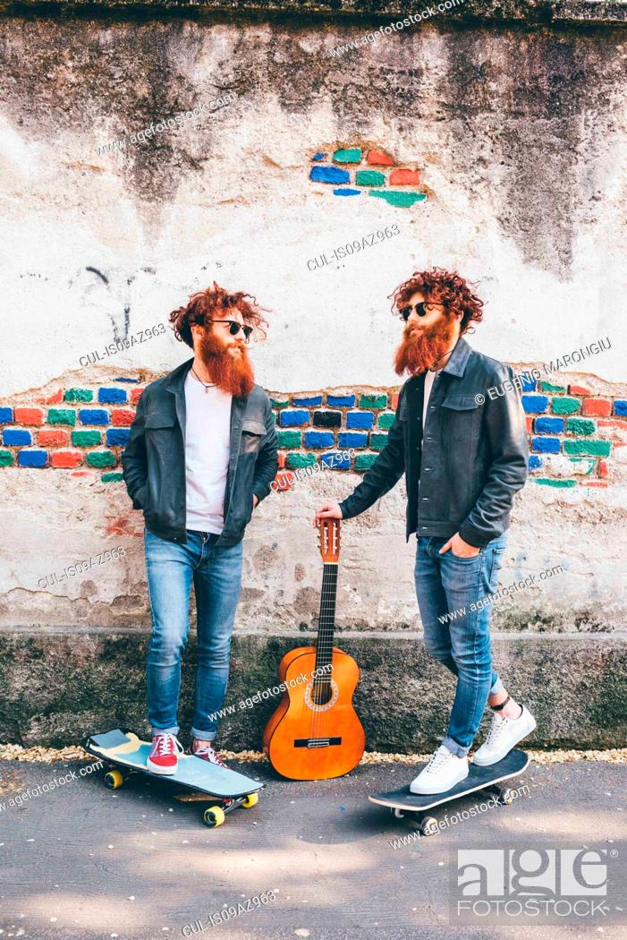 Imagen: Young male hipster twins with red hair and beards on sidewalk with skateboards.