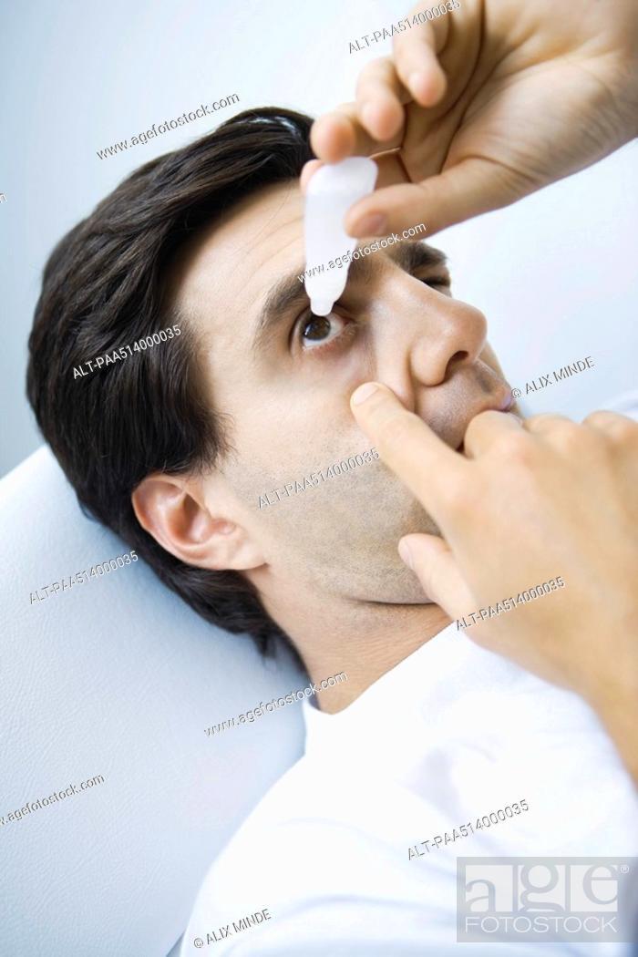 Stock Photo: Man reclining, putting eyedrops in one eye.