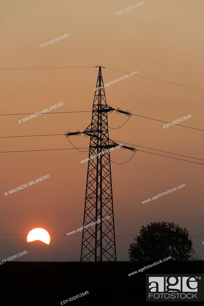 Stock Photo: A sunset with sunshine behind the mountains, an electric trellis flanked by a tree, all in a very hot backlight.