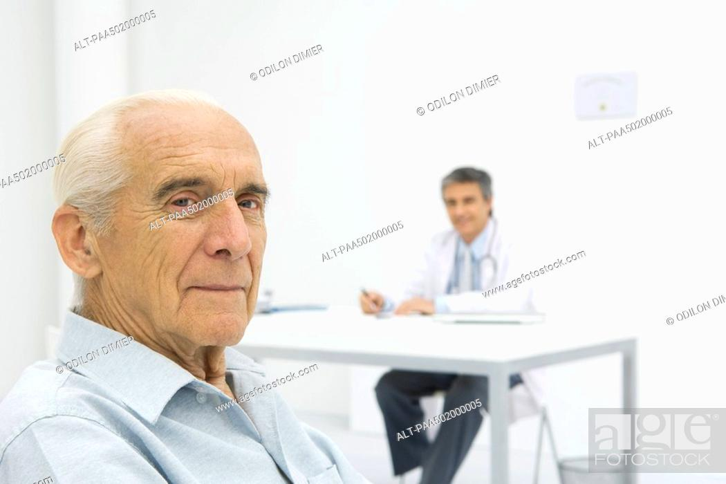 Stock Photo: Doctor working at desk, focus on senior patient in foreground.