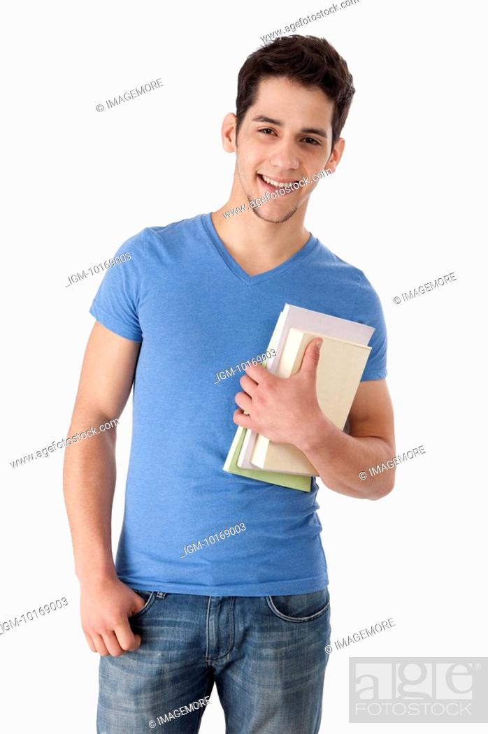 Stock Photo: Young man holding books, smiling.