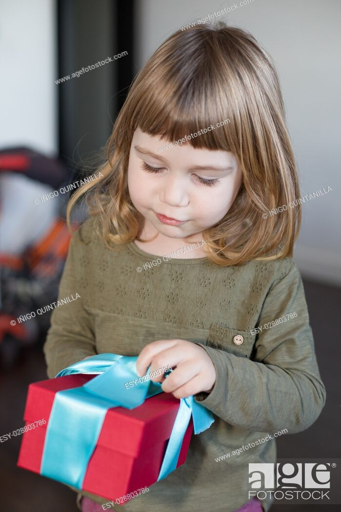 Stock Photo: portrait of three years old caucasian blonde child, with green shirt, and red and blue gift box in hands indoors.