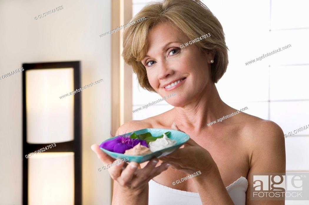 Stock Photo: Portrait of a mature woman holding a bowl and smiling.