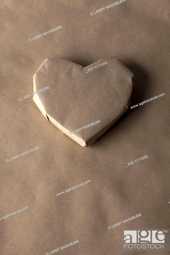 Stock Photo: A heart shaped object wrapped in brown paper.