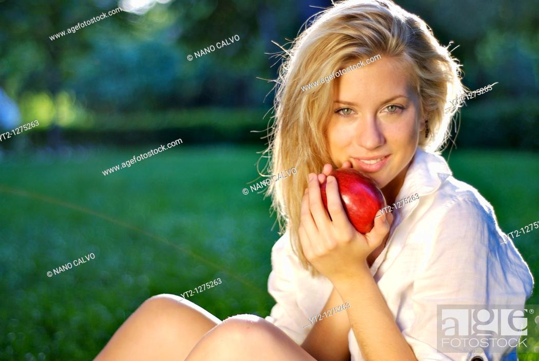 Stock Photo: Attractive young blonde in nature, holding a fresh apple.