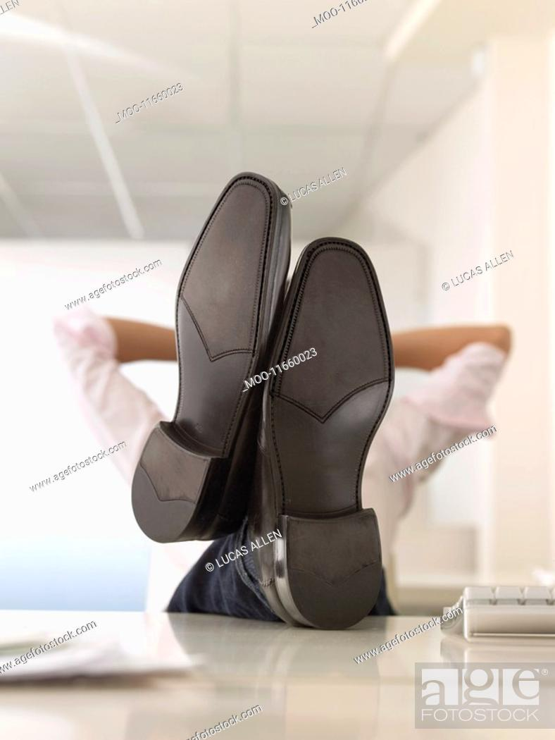 Stock Photo: Businessman with Feet Up on Desk obscured face.