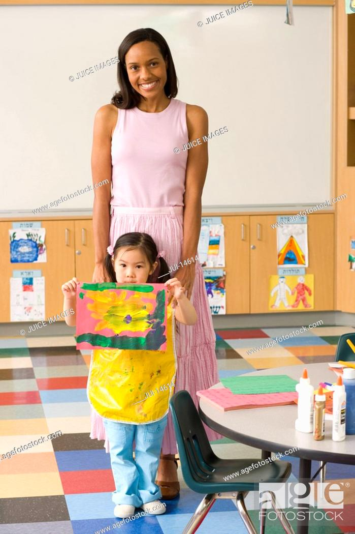Stock Photo: Nursery teacher by girl 3-5 with painting, smiling, portrait.