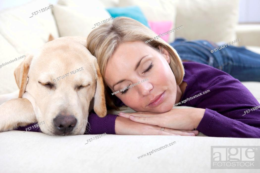 Stock Photo: Young woman lying on a sofa with her Dog.