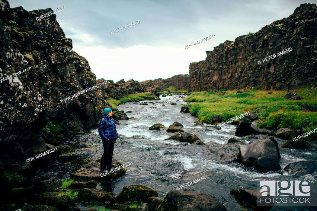 Imagen: Mid adult woman standing on rock on riverbed, looking away, Iceland.