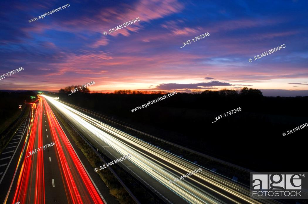 Stock Photo: light trails at night on a busy main road.
