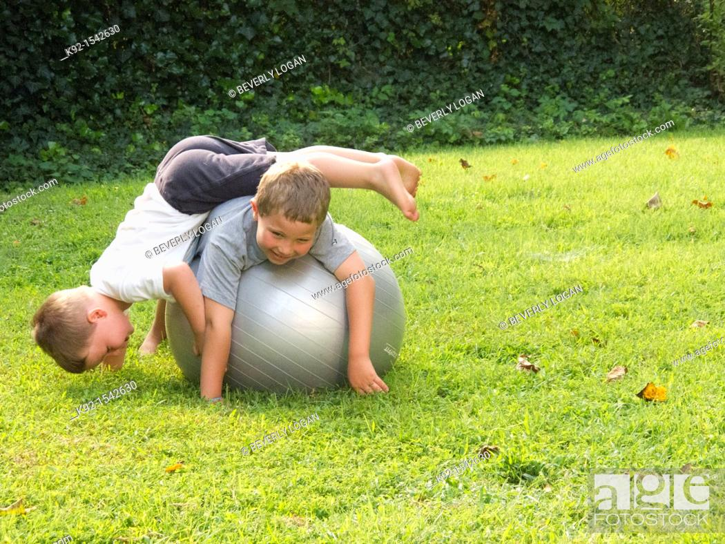Stock Photo: Boys playing on an exercise ball.