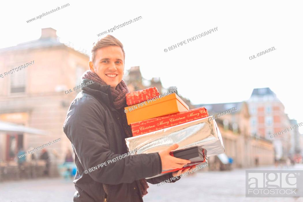 Stock Photo: Portrait of young man carrying stack of xmas presents in Covent Garden, London, UK.