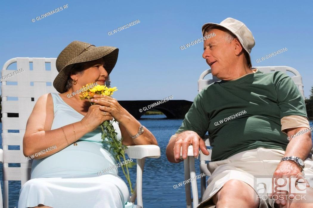 Stock Photo: Senior couple sitting at the lakeside and looking at each other.