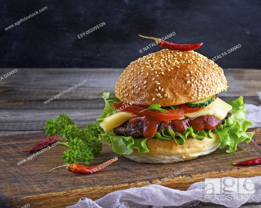 Stock Photo: fresh homemade burger with lettuce, cheese, onion and tomato on a rustic wooden board on a dark background.