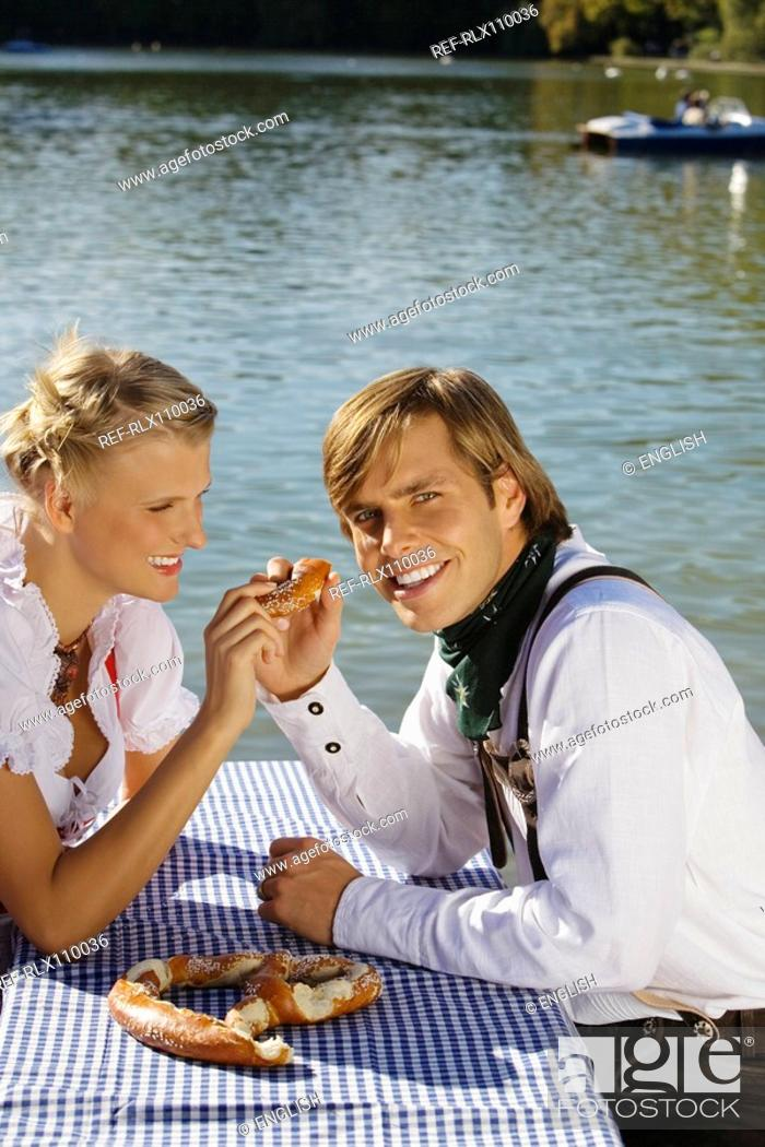 Photo de stock: Young couple in traditional Bavarian outfit, eating Pretzel, Munich.