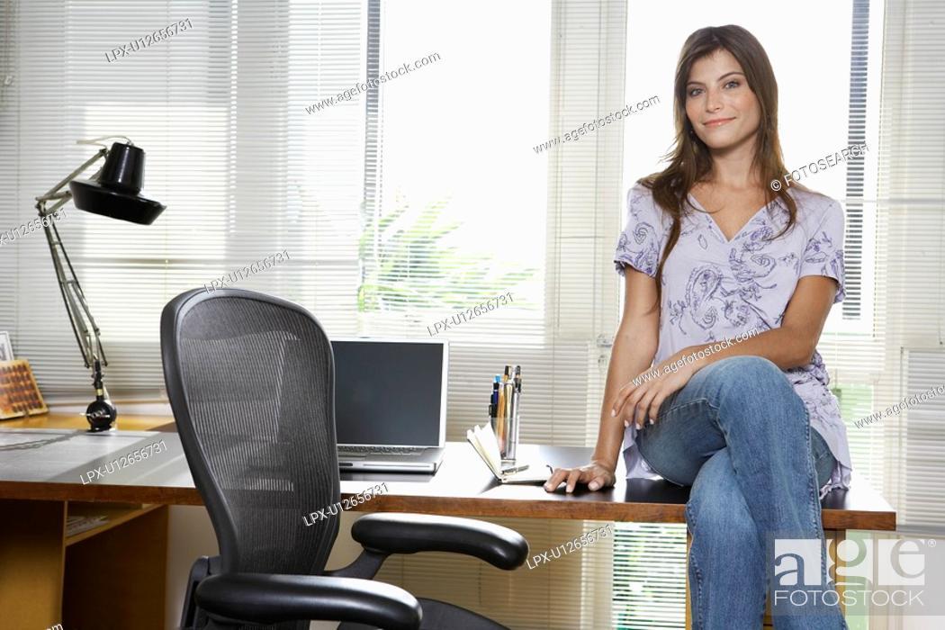 Stock Photo: Young entrepreneur sitting on desk portrait.