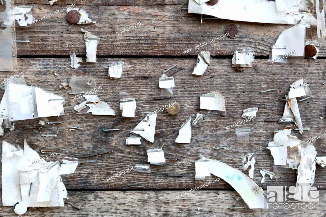 Stock Photo: Detail of staples, thumbtacks and ripped paper on a wooden wall.