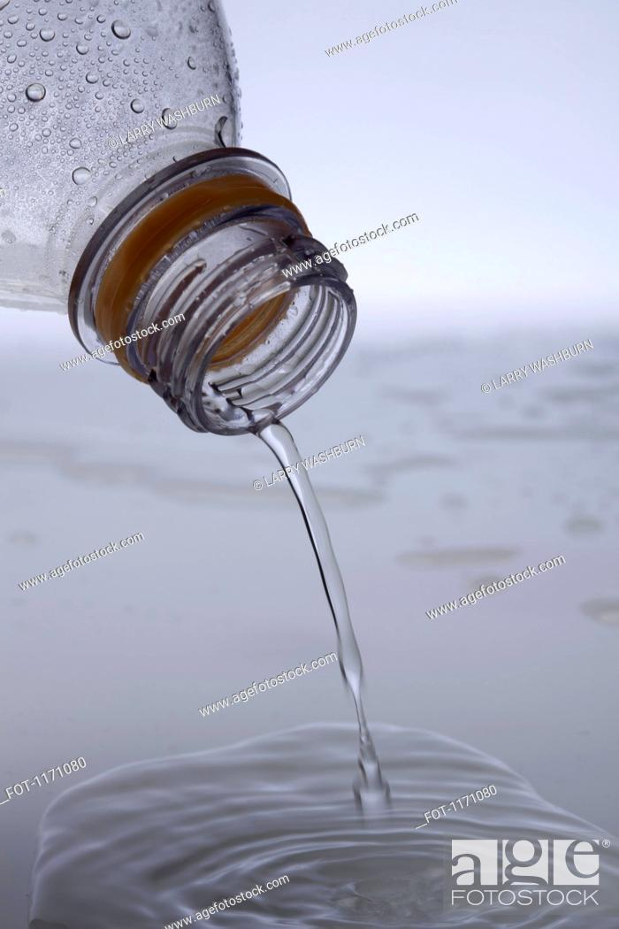 Stock Photo: Water pouring out of a plastic water bottle, close-up.